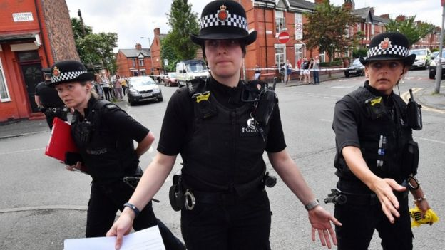 Police put up a corden as they attend the scene of a raid in the Moss Side area of Manchester
