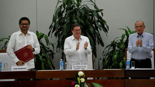 Cuban Foreign Affairs Minister Bruno Rodriguez Parrilla (C) appplauds after FARC-EP leftist guerrilla commander Ivan Marquez (L) and the head of the Colombian delegation for peace talks Humberto de la Calle (R) signed a new peace agreement in Havana, on November 12, 2016.