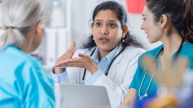 Una doctora hablando con su equipo.