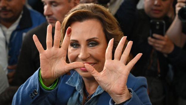 8月11日,桑德拉托雷斯在危地马拉城的一个投票站投票后展示了她的双手