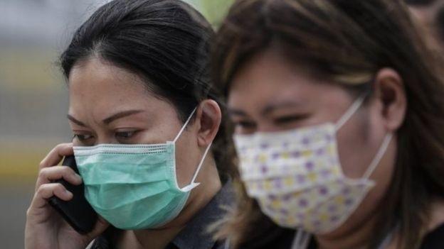 Dua orang mengenakan masker di Jakarta, di tengah kepastian soal dua kasus virus corona.