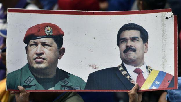 Manifestante segura pôster com fotos de Hugo Chávez e Nicolás Maduro
