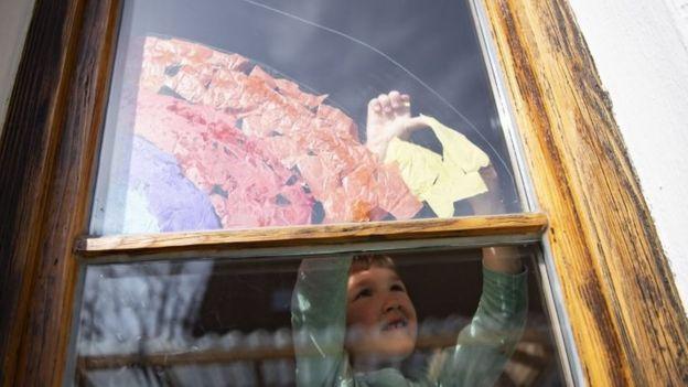 一个五岁的女孩,将一根由彩色纸片制成的彩虹粘在巴伐利亚慕尼黑的一个窗户上