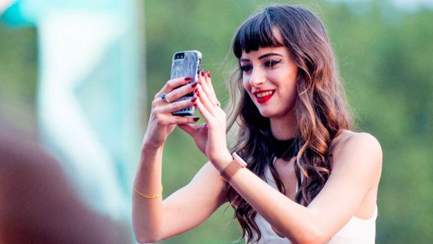 Adolescente con un celular usando Snapchat