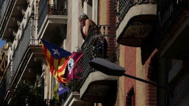 A Catalan separatist flag hangs from a balcony as a man smokes in Barcelona, Spain October 11, 2017