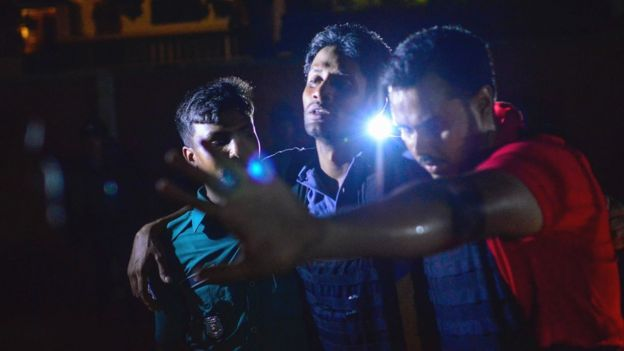 Bangladeshi policeman that was injured during an attack on an upscale restaurant is helped by others in Dhaka on July 1, 2016.