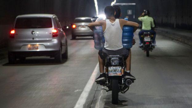 Homem carrega galões de água em cima de moto
