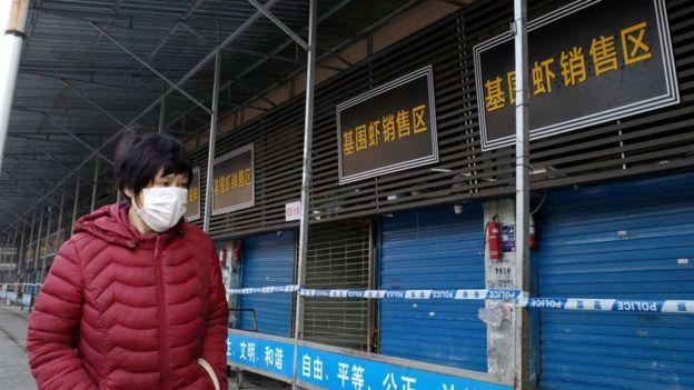 Una mujer usando una mascarilla camina cerca de un mercado cerrado en China.