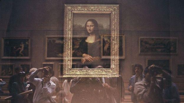 La Mona Lisa detrás de su protección de vidrio a prueba de balas con turistas japoneses en el Museo del Louvre.