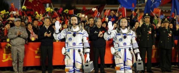 Astronautas chinos Jing Haipeng (derecha) y Chen Dong antes de embarcarse en la nave espacial Shenzhou 11 en el Centro de Lanzamiento de Satélites de Jiuquan, en el noroeste de China, el 17 de octubre de 2016.