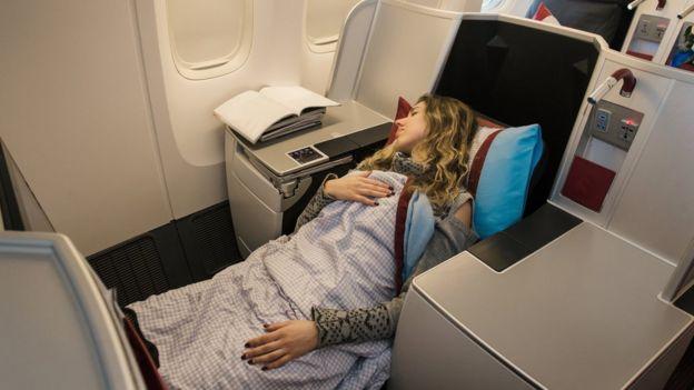 Una mujer duerme en un asiento de primera clase de un avión