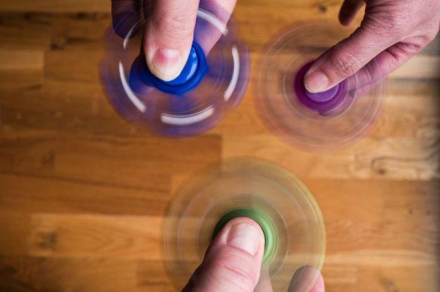 Tres personas hacen girar sus fidget spinners