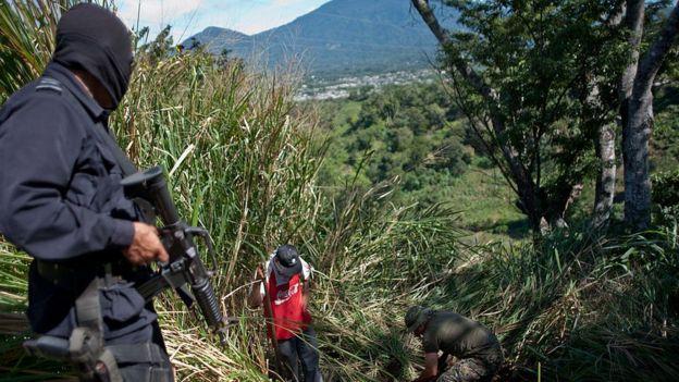 Policía mira una exhumación en El Salvador