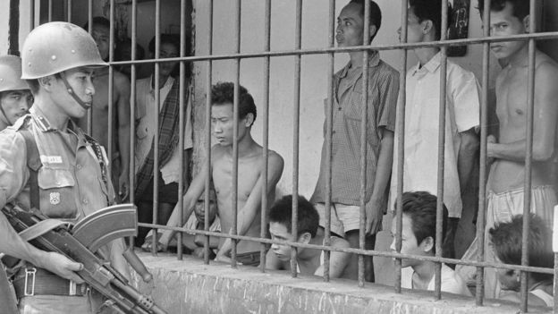 1965 - جندي يراقب افراد يشتبه في أنهم شيوعيون