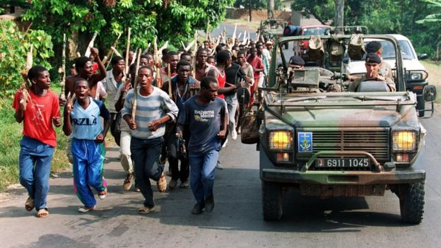 A file picture taken 27 June 1994 shows French soldiers on patrol passing ethnic Hutu troops from the Rwandan government forces, near Gisenyie, about 10km from the border with DR Congo, then Zaire