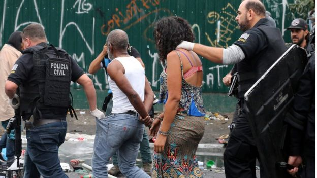 Mulher conduzida por policial em ação na cracolândia