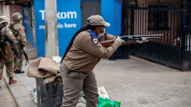 A Gauteng Traffic Police officer shoots rubber bullets to urge residents to go inside during a mixed patrol of South African National Defence Force (SANDF) and Gauteng Traffic Police in Alexandra, Johannesburg