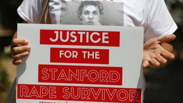"A woman holds a sign saying ""Justice for the Stanford Rape survivor"""