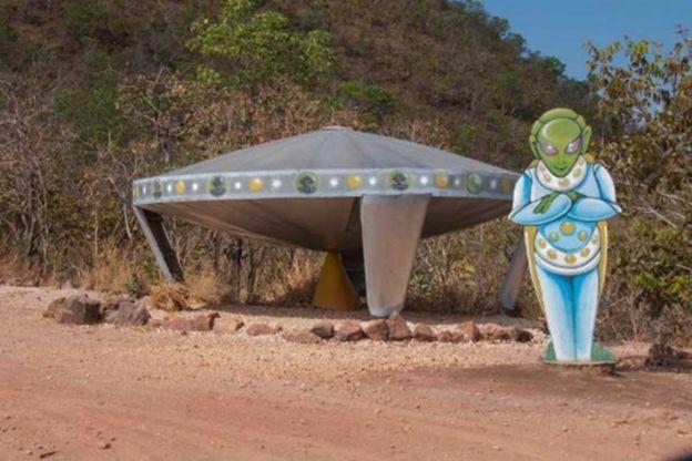 Imagem de escultura representando um óvni - ao lado, um painel representando um alienígena