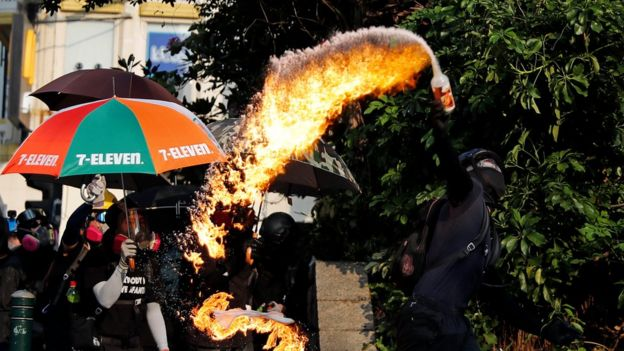 An arc of fire streams from a petrol bomb in a bottle as a black-clad protester tosses it