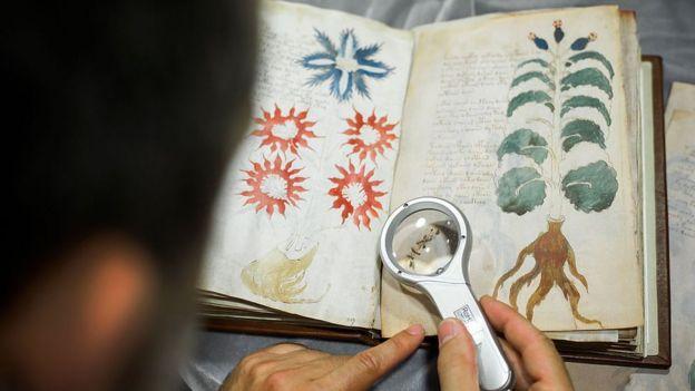 Homem olhando o manuscrito Voynich com uma lupa