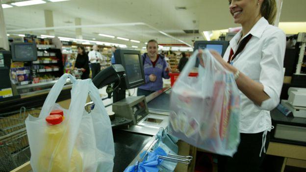 Cajera en un supermercado colocando artículos en bolas de plástico