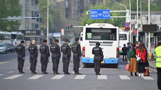 Police officers and officials stop and pay their respects during a three minutes of silence to mourn those who died in the fight against the pandemic