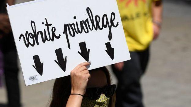Mujer con una pancarta que critica el privilegio blanco en Barcelona.