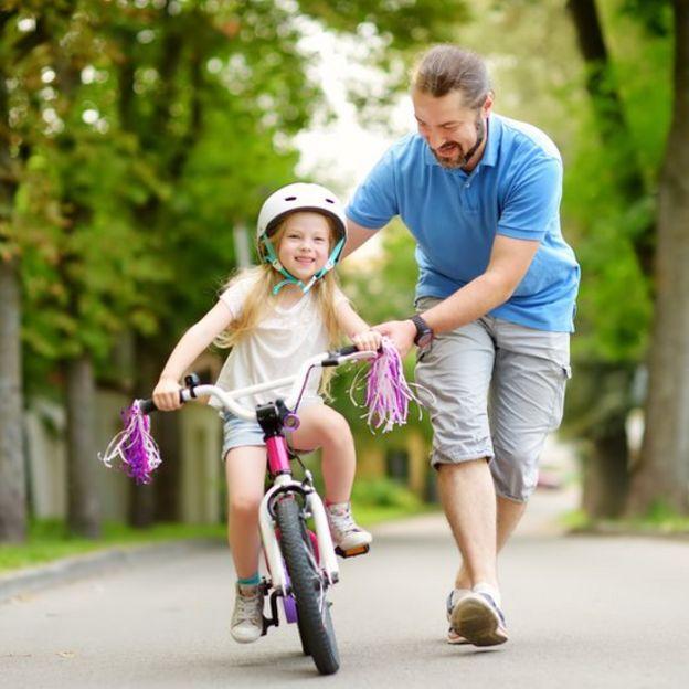 Padre y niña en bicicleta.