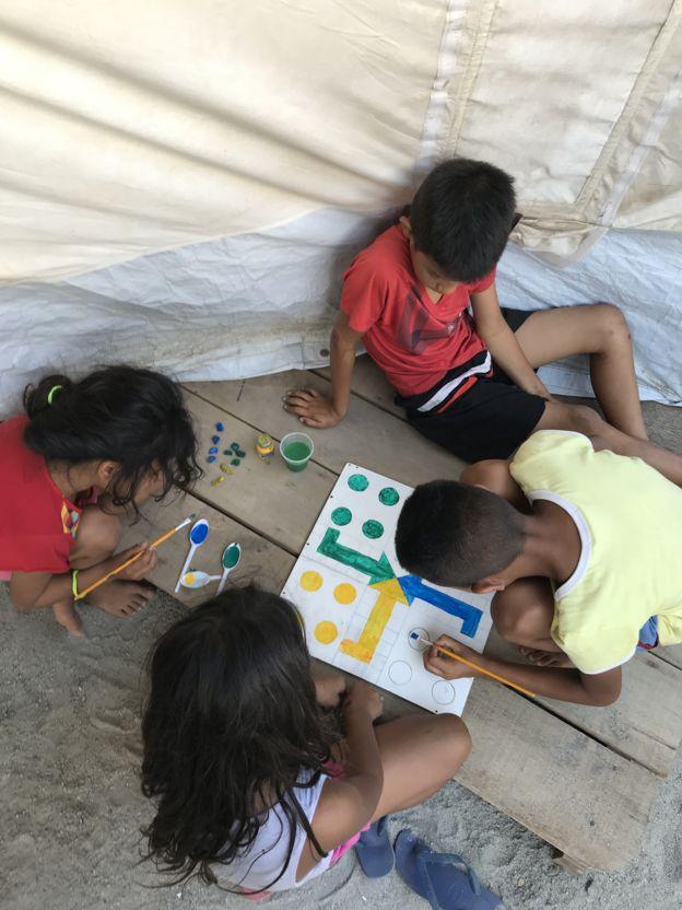 Niños haciendo su propio tablero de juego en Boa Vista.
