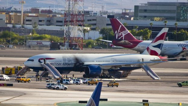 The plane stands on runway surrounded by emergency vehicles at McCarran International Airport following a fire onboard on 8 September 2015