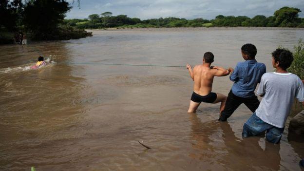Jóvenes sujetan una cuerda para facilitar el paso por el río Goascorán.