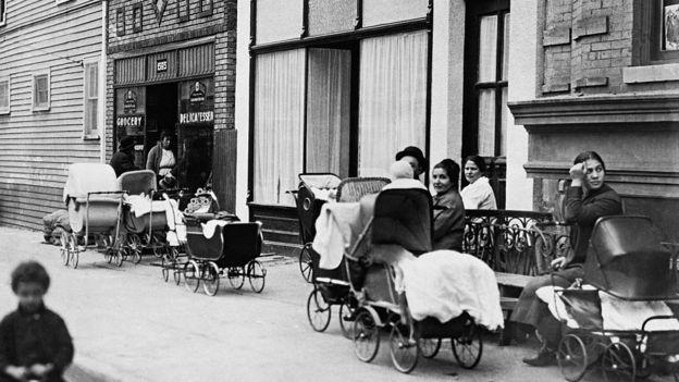 Mujeres y hombres sentados con cochecitos frente a la Clínica Sanger