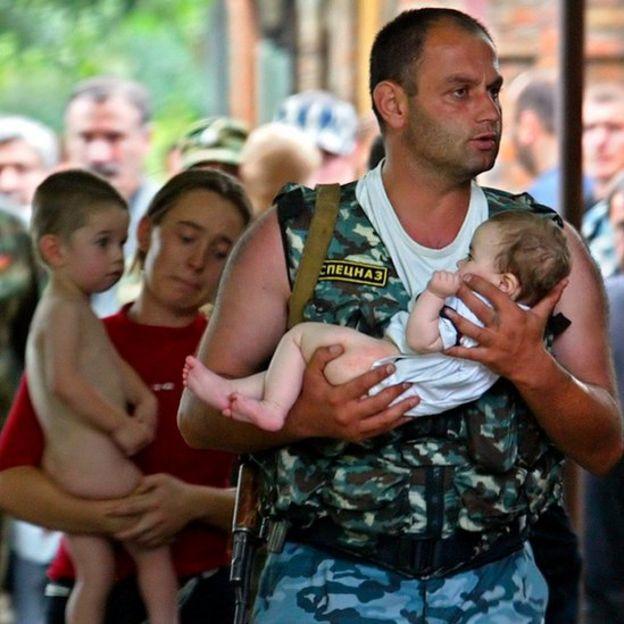 Um soldado carrega um bebê