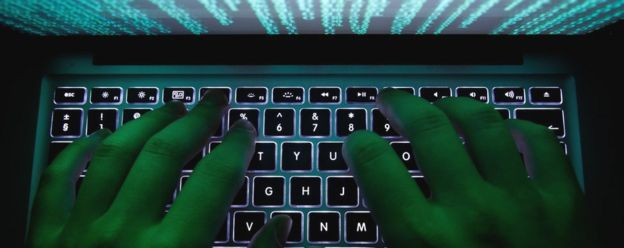 A man's hands typing on a laptop keyboard