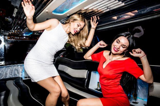 Dos mujeres bailando dentro de una limusina.