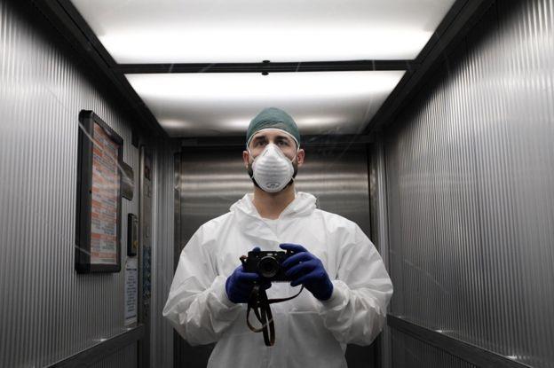 Paolo Miranda, com máscara e jaleco, tira uma foto de si mesmo com câmera em espelho de elevador