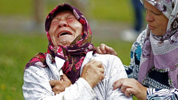 Familiar de víctimas de Srebrenica llorando amargamente mientras otra mujer intenta consolarla
