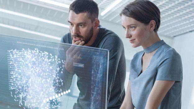 homem e mulher olham para tela