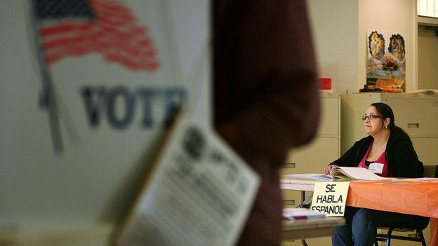 Una miembro de mesa de votación en Estados Unidos sentada en una mesa con un cartel que cuelga y dice Se habla español