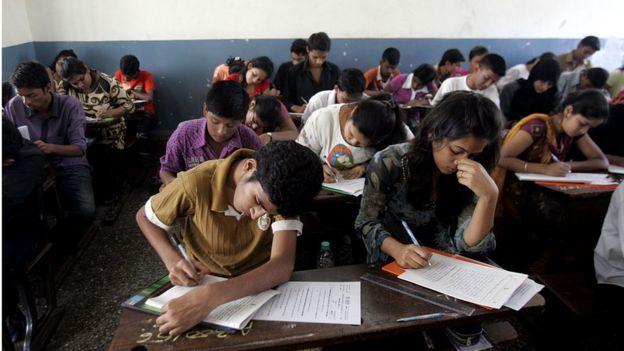 Varios escolares resuelven un examen en un salón humilde