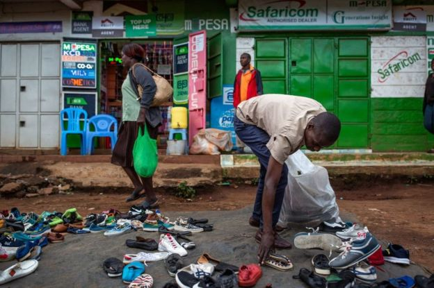 Man gathering shoes in a market