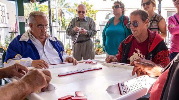 Cubanos juegan dominó en la Calle 8 de Miami.