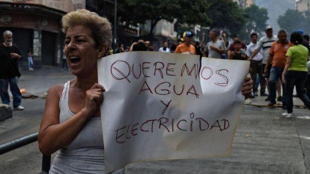 """Una mujer con un cartel que dice """"Queremos electricidad y agua""""."""