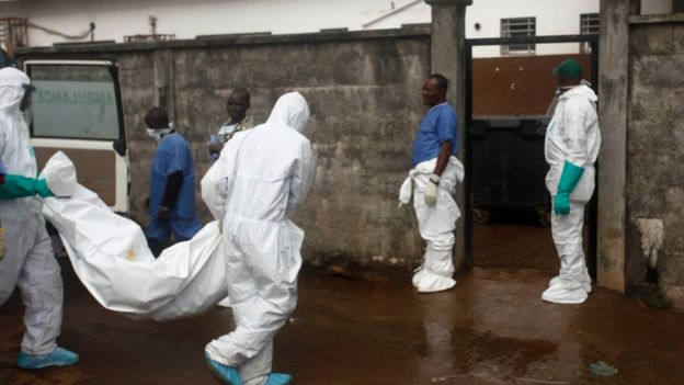 Members of a burial team carry a body from an ambulance into a morgue in Freetown