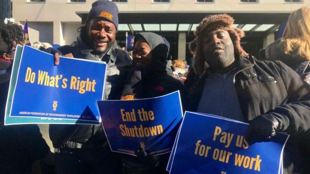 人口普查局雇员希尔(左)与同事参与抗议政府停摆的游行。