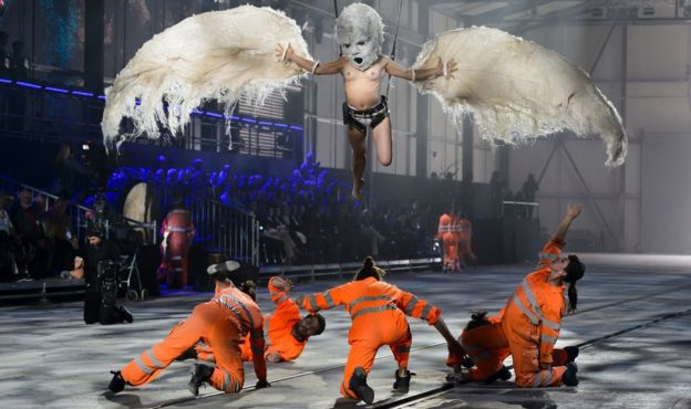 Artists perform during a show on the opening day of the Gotthard rail tunnel - men playing construction workers and a bird above them - 1 June 2016