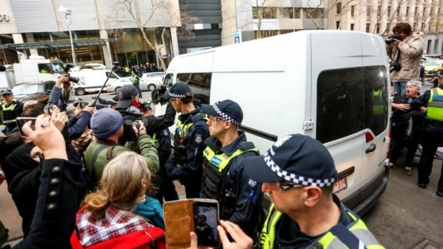 A white van carrying George Pell leaves court, beside police officers, media representatives and members of the public