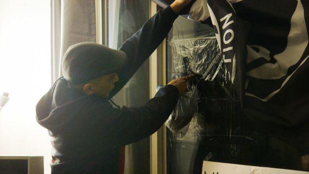 Luis señala el agujero en la ventana del frente de su casa