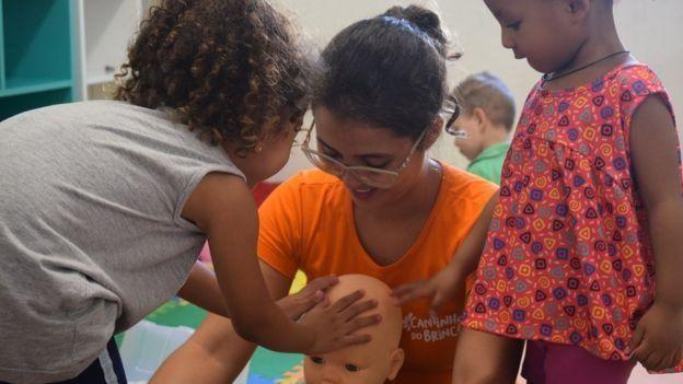 Una profesora del proyecto piloto Cantinho do Brincar, junto a varios niños.